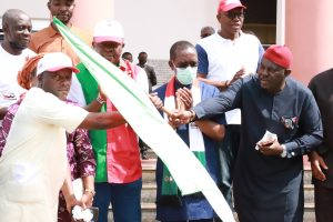 Delta State Governor, Senator Dr. Ifeanyi Okowa (2nd right) looks on as the PDP Chairman, Anambra state, Hon. Ndubuisi Nwobu (right) hands over PDP flag to Mr. Magnus Eziokwu who led APGA decampees to PDP when the Party's (PDP) Governorship candidate, Valentine Ozigbo (2nd left), led them and his other supporters on a visit to the Governor in Government House, Asaba.